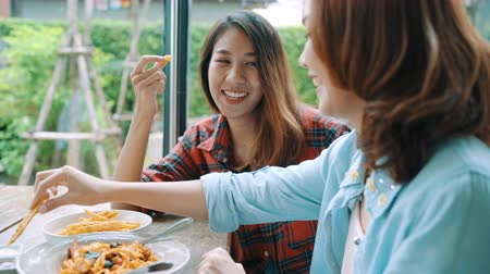 macarrão : Beautiful happy Asian women lesbian lgbt couple sitting each side eating a plate of Italian seafood spaghetti and french fries at restaurant or cafe while smiling and looking at food. Vídeos