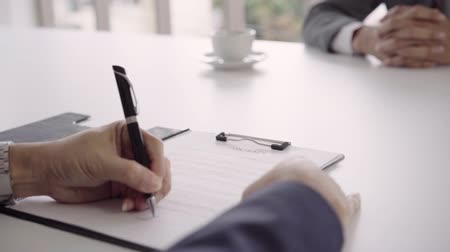 acceptance : Slow motion - Smart handsome businessmen meeting in workplace with his colleague and signing a contract, recruitment and agreement concept. Male making a deal.