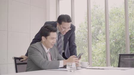 together trust : Slow motion - Smart handsome businessmen using smartphone to check stock market data. Male checking stock charts and feeling happy when it uptrend. Stock Footage