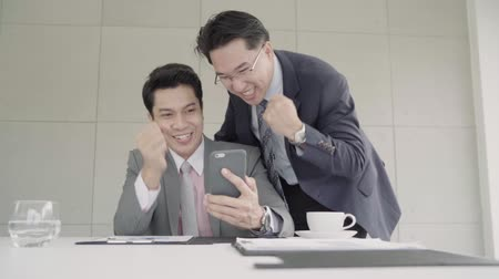 партнеры : Slow motion - Smart handsome businessmen using smartphone to check stock market data. Male checking stock charts and feeling happy when it uptrend. Стоковые видеозаписи