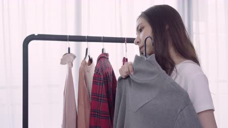 wieszak : Home wardrobe or clothing shop changing room. Mixed race Asian and Caucasian young woman choosing her fashion outfit clothes in closet at home or store. Girl think what to wear sweater.
