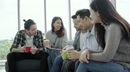 discussão : Multiethnic creative team diversity of young people group team holding coffee cups and discussing ideas meeting with tablet sitting on the couch at office. Coffee break time at creative office. Stock Footage