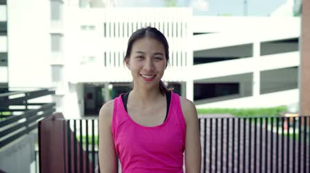 задумчивый : Slow motion - Healthy beautiful young Asian runner woman feeling happy smiling and looking to camera after running on street in urban city. Lifestyle fit and active women exercise in the city concept. Стоковые видеозаписи