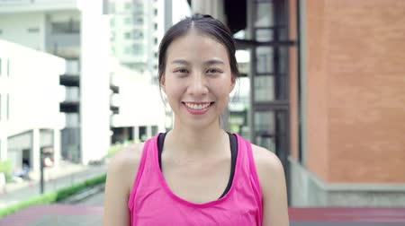 задумчивый : Healthy beautiful young Asian runner woman feeling happy smiling and looking to camera after running on street in urban city. Lifestyle fit and active women exercise in the city concept.