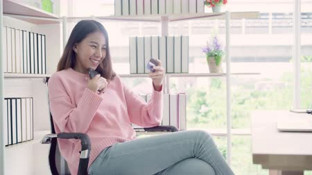 snadný : Beautiful Asian woman using smartphone buying online shopping by credit card while wear sweater sitting on desk in living room at home. Lifestyle woman at home concept.