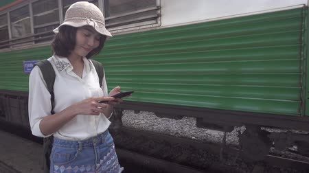 hátizsákkal : Slow motion - Traveler backpacker Asian woman travel in Bangkok, Thailand. Happy young female using smartphone for talking, reading and texting at train station.