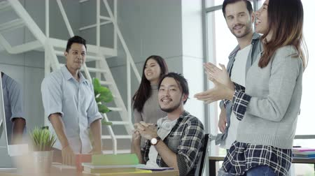 humor : Successful handsome smart Asian creative businessman and his colleagues arms raised celebrating success Operating Result feeling happy in office. Lifestyle business man in his workplace concept. Stock mozgókép