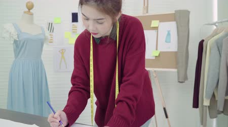 manekin : Young Asian woman fashion designer drawing using pencil and looking at paper while working in the workshop studio. Wideo