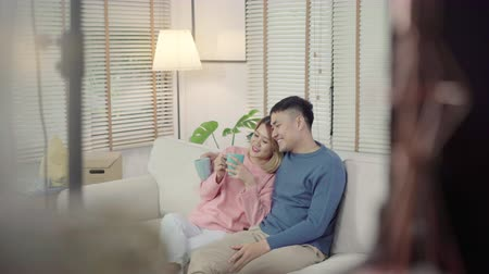 resting : Attractive Asian sweet couple enjoy love moment drinking warm cup of coffee or tea in their hands on sofa in the living room at home. Husband and his wife relaxing at home concept.