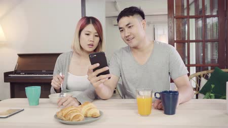 jeść : Attractive young Asian couple distracted at table with newspaper and cell phone while eating breakfast. Excited young Asian couple surprised by unbelievably good news, happy family amazed by internet.