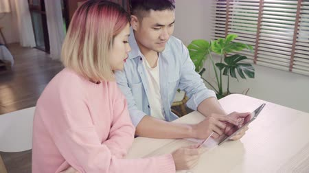 дебет : Young Asian family couple using tablet discussing news or doing online shopping sitting together on desk at home on weekend together, serious man and woman browsing web searching for new sale offers.