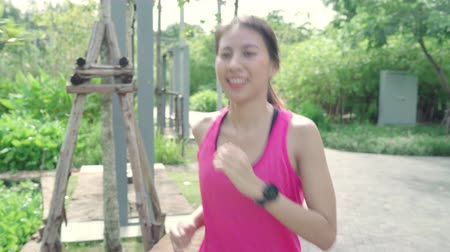 girl : Healthy beautiful young Asian runner woman in sports clothing running and jogging on street in urban city park. Lifestyle fit and active women exercise in the city concept. Stock Footage