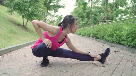 спринт : Healthy beautiful young Asian Athlete women in sports clothing legs warming and stretching her arms to ready for running on street in urban city park. Lifestyle active women exercise in city concept.