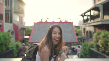 raised : Slow motion - Cheerful beautiful young Asian backpacker blogger woman feeling happy dancing on street while traveling at Chinatown in Beijing, China. Lifestyle backpack tourist travel holiday concept.