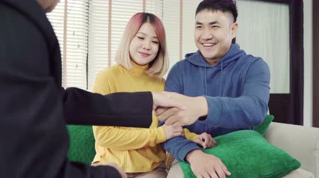 magánélet : Happy young Asian couple and realtor agent. Cheerful young man signing some documents and handshaking with broker while sitting at desk. Signing good condition contract.
