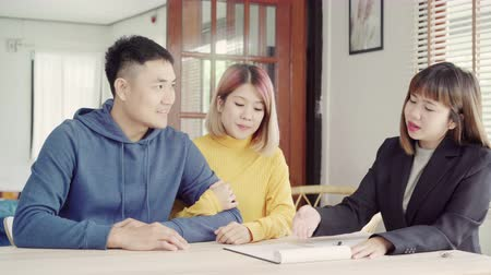 инвестирование : Happy young Asian couple and realtor agent. Cheerful young man signing some documents while sitting at desk together with his wife. Buying new house real estate. Signing good condition contract.