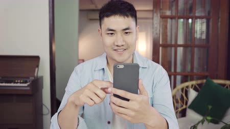 ücretli : Asian man using smartphone for online shopping in internet at living room home. Asia man sitting at table in casual clothes, relaxing and buying goods easily. E Commerce concepts.