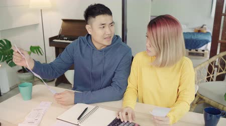 faktura : Young stressed asian couple managing finances, reviewing their bank accounts using laptop computer and calculator at modern home. Woman and man doing paperwork together, paying taxes online.