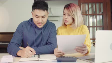 makbuz : Young asian couple managing finances, reviewing their bank accounts using laptop computer and calculator at modern home. Woman and man doing paperwork together, paying taxes online on notebook pc. Stok Video