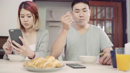 distraído : Attractive young Asian couple distracted at table with newspaper and cell phone while eating breakfast. Excited young Asian couple surprised by unbelievably good news, happy family amazed by internet.