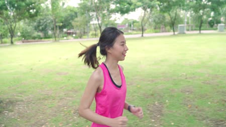 mladé ženy : Slow motion - Healthy beautiful young Asian runner woman in sports clothing running and jogging on street in urban city park. Lifestyle fit and active women exercise in the city concept.