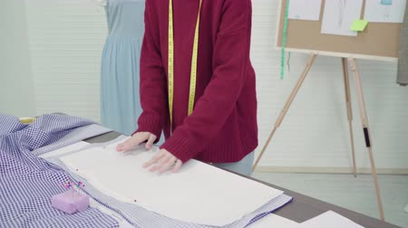 sme : Professional beautiful Asian female fashion designer working with fabric sketches and drawing clothing design at the studio. Lifestyle women working concept.