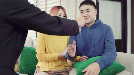 advisor : Happy young Asian couple and realtor agent. Cheerful young man signing some documents and handshaking with broker while sitting at desk. Signing good condition contract.