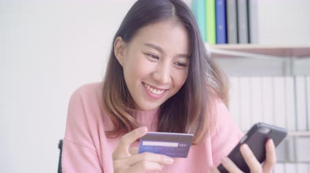 カード : Beautiful Asian woman using smartphone buying online shopping by credit card while wear sweater sitting on desk in living room at home. Lifestyle woman at home concept.