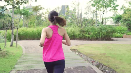 спортивная одежда : Healthy beautiful young Asian runner woman in sports clothing running and jogging on street in urban city park. Lifestyle fit and active women exercise in the city concept. Стоковые видеозаписи