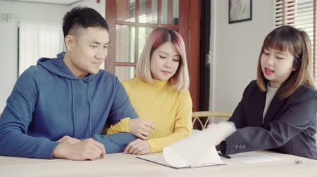 magánélet : Happy young Asian couple and realtor agent. Cheerful young man signing some documents while sitting at desk together with his wife. Buying new house real estate. Signing good condition contract.