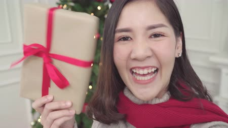 picture box : Cheerful happy young Asian woman using smartphone selfie with christmas tree decorate her living room at home in Christmas Festival. Lifestyle woman celebrate Christmas and New year concept.