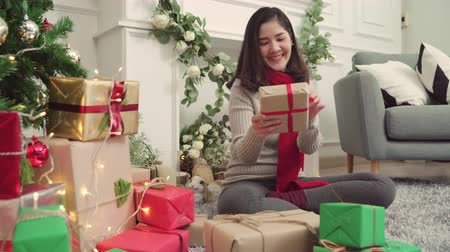 csomagolás : Cheerful happy young Asian woman packing and wrapping Christmas present decorate her living room at home in Christmas Festival. Lifestyle woman celebrate Christmas and New year concept.