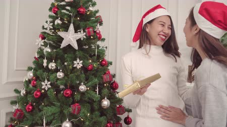 confortável : Group of cheerful happy young Asian women giving christmas gifts to each other in her living room at home in Christmas Festival. Lifestyle women celebrate Christmas and New year concept.