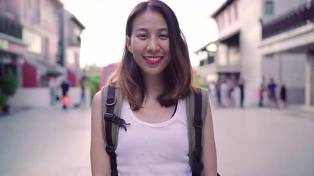 задумчивый : Cheerful beautiful young Asian backpacker woman feeling happy smiling to camera while traveling at Chinatown in Beijing, China. Lifestyle backpack tourist travel holiday concept.