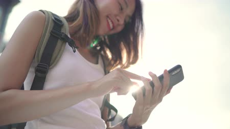 destinace : Cheerful Asian backpacker blogger woman using smartphone for direction and looking on location map while traveling at Chinatown in Beijing, China. Lifestyle backpack tourist travel holiday concept.