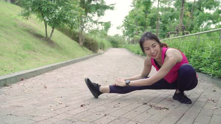 esneme : Healthy beautiful young Asian Athlete women in sports clothing legs warming and stretching her arms to ready for running on street in urban city park. Lifestyle active women exercise in city concept.