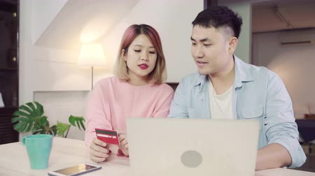 debet : Young Asian family couple using laptop discussing news or doing online shopping sitting together on desk at home on weekend together, serious man and woman browsing web searching for new sale offers.