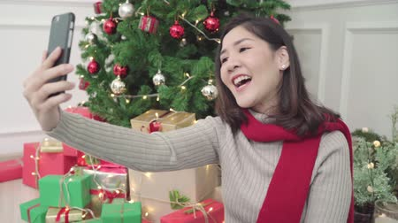 ano novo chinês : Cheerful happy young Asian woman using smartphone selfie with christmas tree decorate her living room at home in Christmas Festival. Lifestyle woman celebrate Christmas and New year concept.
