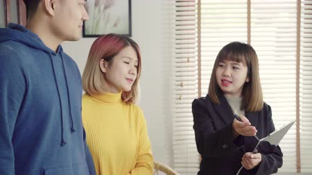 adó : Happy young Asian couple and realtor agent. Cheerful young man signing some documents and handshaking with broker while sitting at desk. Signing good condition contract.