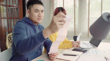 nyugta : Young stressed asian couple managing finances, reviewing their bank accounts using laptop computer and calculator at modern home. Woman and man doing paperwork together, paying taxes online.