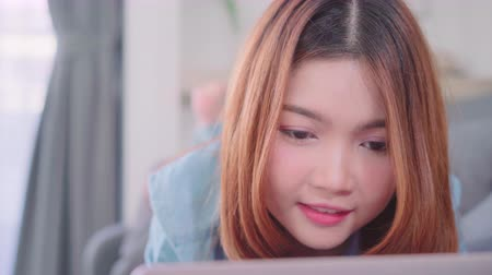 hajló : Portrait of beautiful attractive young smiling Asian woman using computer or laptop while lying on the sofa when relax in living room at home. Enjoying time lifestyle women at home concept. Stock mozgókép
