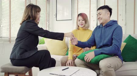 makler : Happy young Asian couple and realtor agent. Cheerful young man signing some documents and handshaking with broker while sitting at desk. Signing good condition contract.