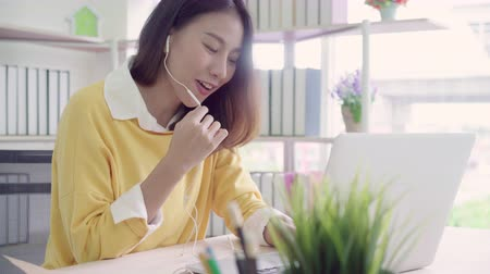 elszánt : Beautiful smart business Asian woman in smart casual wear working on laptop and talking in a video conference on line with a headset with microphone in office. Lifestyle women working at home concept.