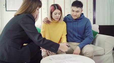 komisyoncu : Happy young Asian couple and realtor agent. Cheerful young man signing some documents while sitting at desk together with his wife. Buying new house real estate. Signing good condition contract.