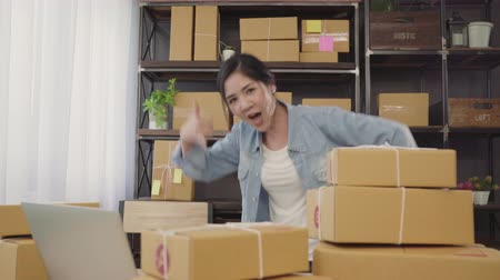sme : Beautiful smart Asian young entrepreneur business woman owner of SME feeling happy dancing while see business achievement. Small business owner at home office concept.