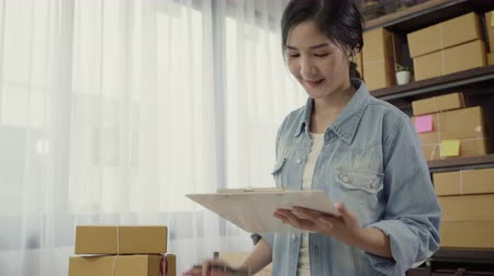 sipariş : Beautiful smart Asian young entrepreneur business woman owner of SME checking product on stock and write on clipboard working at home. Small business owner at home office concept. Stok Video