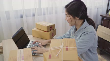 retailer : Beautiful smart Asian young entrepreneur business woman owner of SME online checking product on stock and save to computer working at home. Small business owner at home office concept.