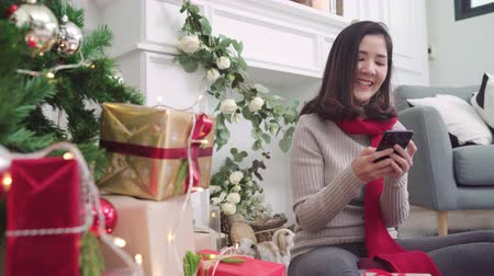居心地のよい : Cheerful happy young Asian woman using smartphone to check social media in her living room at home in Christmas Festival. Lifestyle women celebrate Christmas and New year concept.