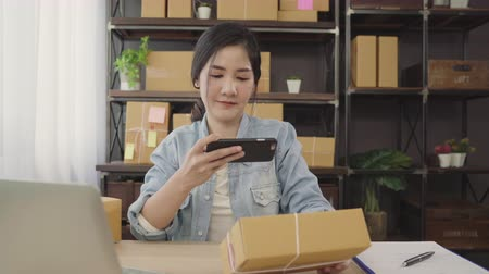qr : Beautiful smart Asian young entrepreneur business woman owner of SME checking product on stock scan qr code working at home. Small business owner at home office concept.