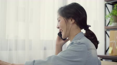 mensageiro : Beautiful smart Asian young entrepreneur business woman owner of SME online using smartphone call receive from customer and using laptop working at home. Small business owner at home office concept. Stock Footage